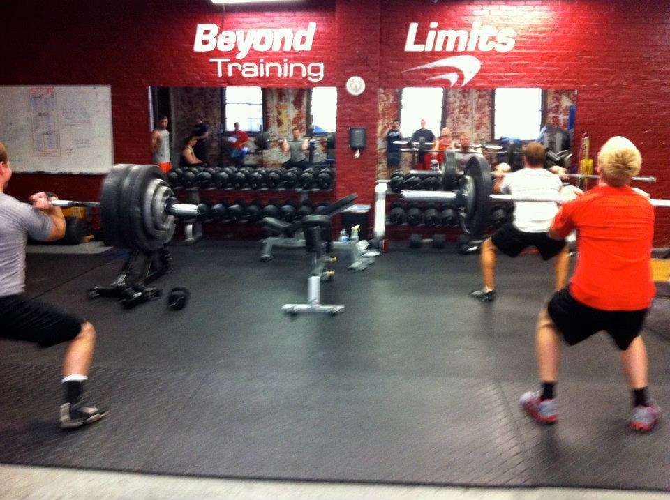 Group Of People Lifting At Beyond Limits Training Gym.